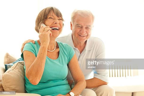Par sênior falando no telefone com os seus amigos e familiares