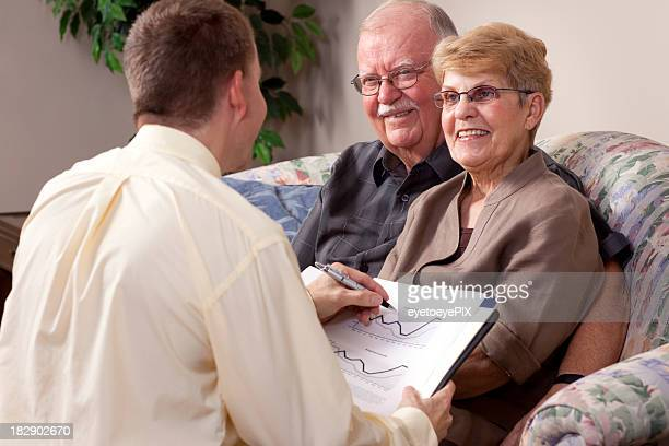 Senior couple speaking with a man holding a book with charts