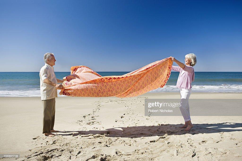 Senior couple spreading blanket on beach : Stock Photo