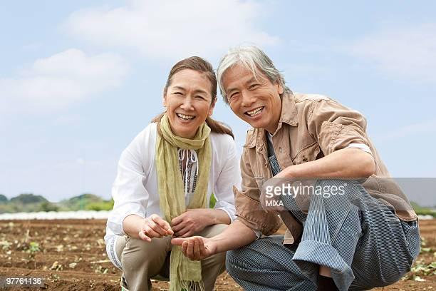 Senior couple squatting on field
