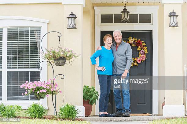 Senior couple standing at front door of home