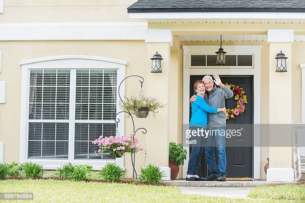 Senior couple standing at front door of home waving