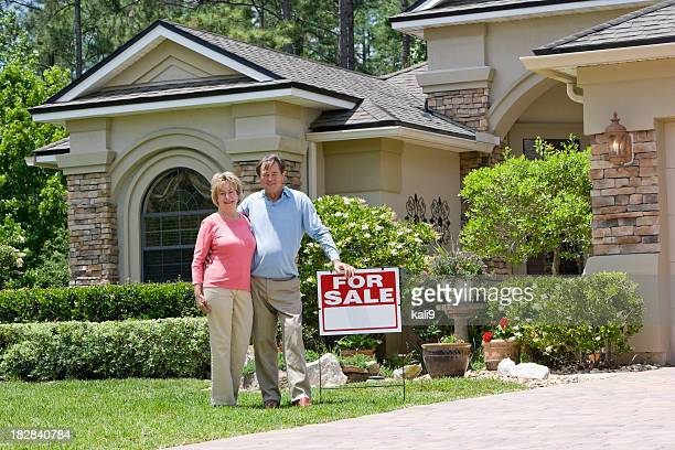 Senior couple standing by For Sale sign on house lawn