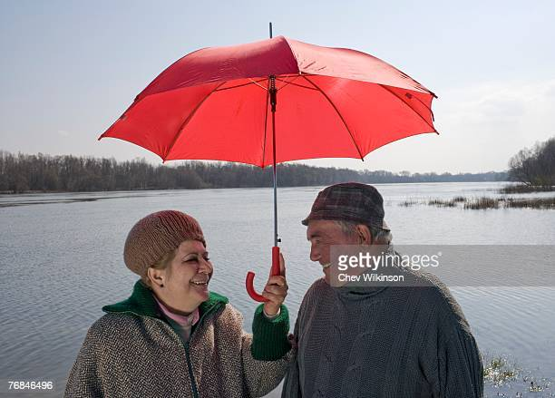 Senior couple standing by river sharing umbrella, smiling