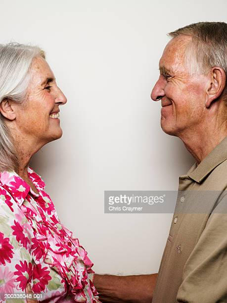 Senior couple standing face to face, smiling, side view