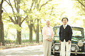 Senior couple standing in front of a car