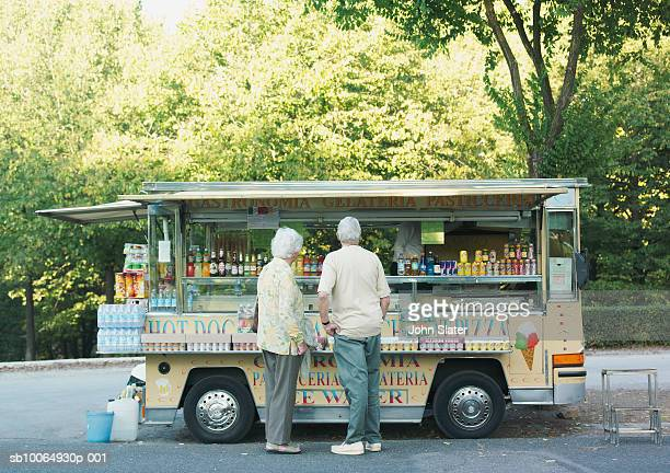 Senior couple standing in front of mobile shop