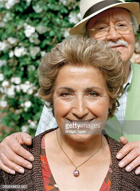 Senior couple standing in garden, smiling, portrait