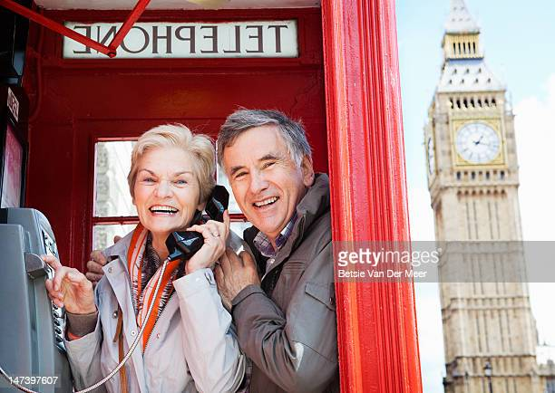 Senior couple standing in red telephone booth.