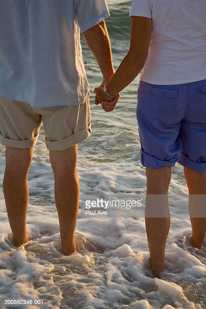 Senior couple standing in surf holding hands, rear view