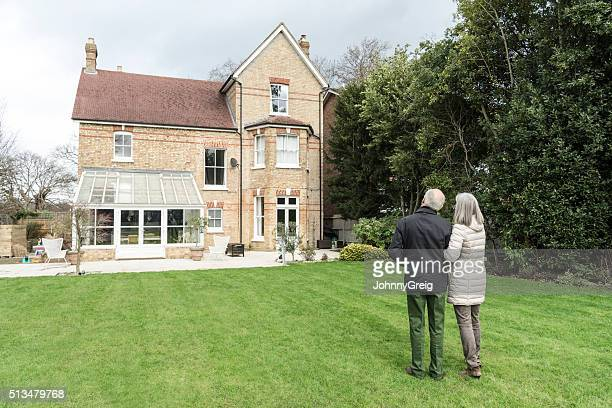 Senior couple standing on lawn outside house