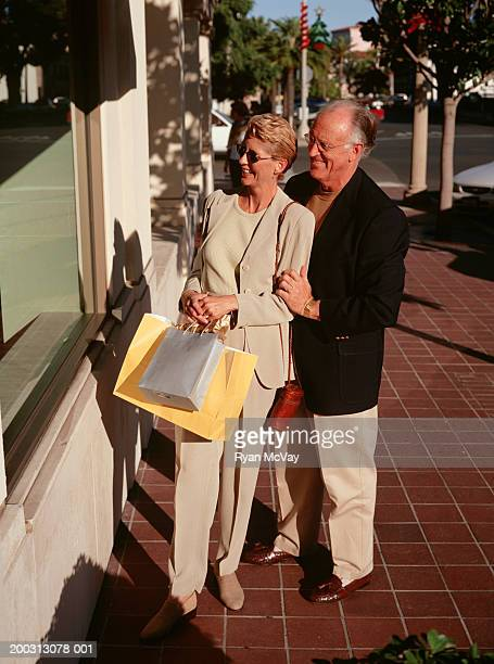 Senior couple standing on sidewalk, window-shopping, elevated view