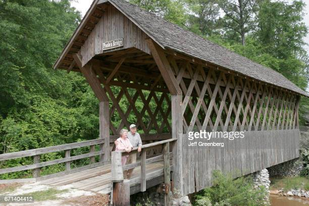 A senior couple standing on the restored Poole's Bridge
