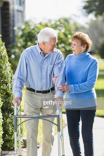 Senior couple standing outdoors, man using walker