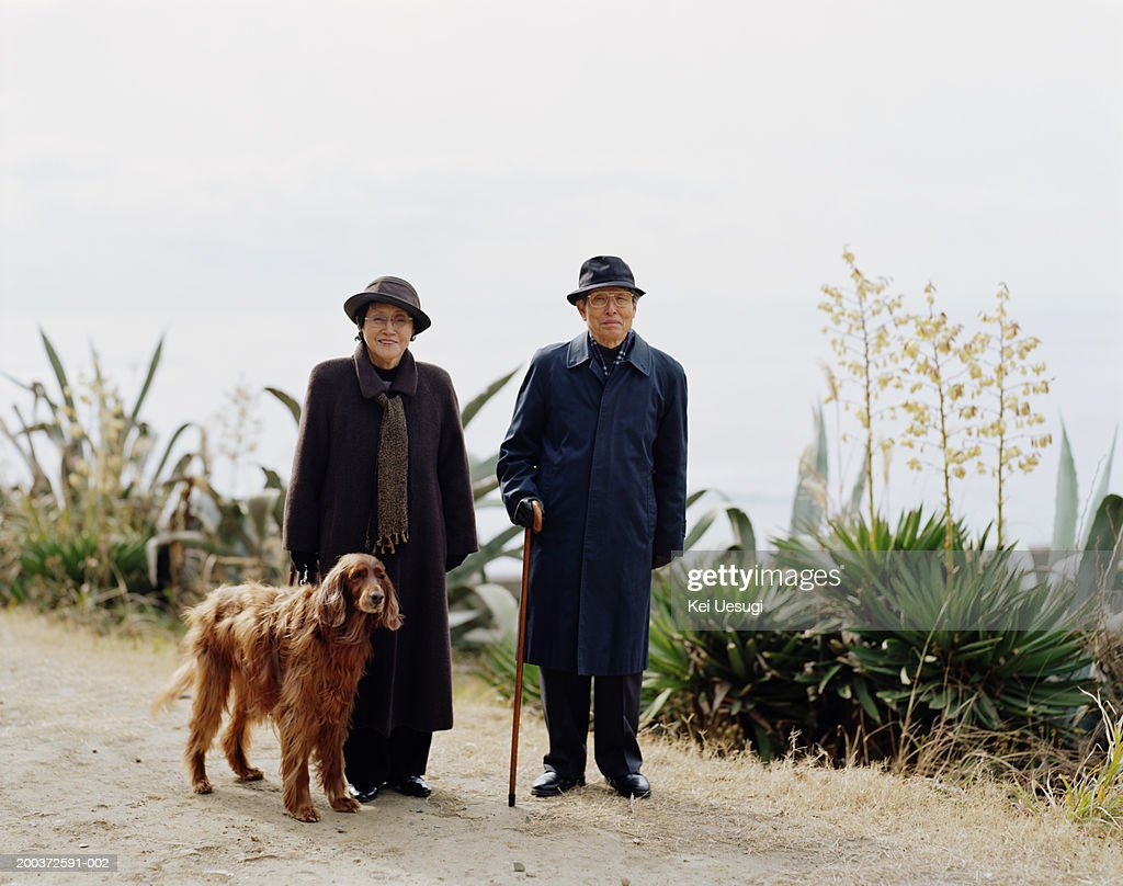 Senior couple standing outdoors with dog, smiling, portrait : Stock Photo
