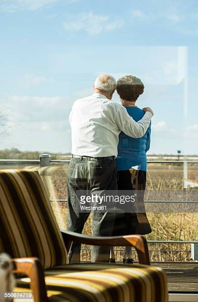 Senior couple standing side by side on terrace