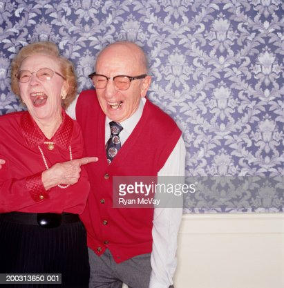 Senior couple standing together laughing, indoors, portrait : Stock Photo
