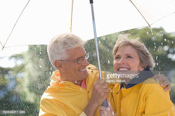 Senior couple standing under umbrella in rain, smiling, close-up