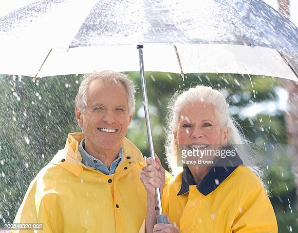 Senior couple standing under umbrella in rain, smiling, portrait
