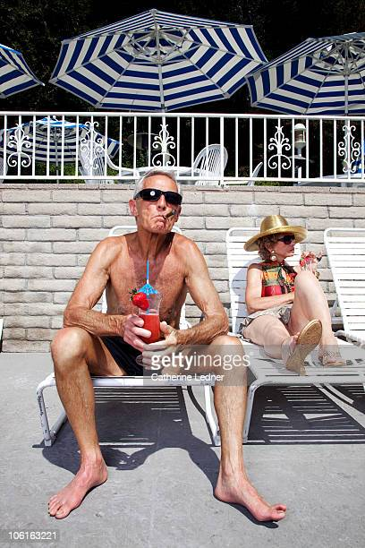 Senior couple sunbathing and enjoying drinks