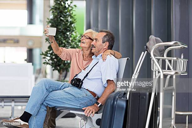 Senior Couple taking a selfie in the airport