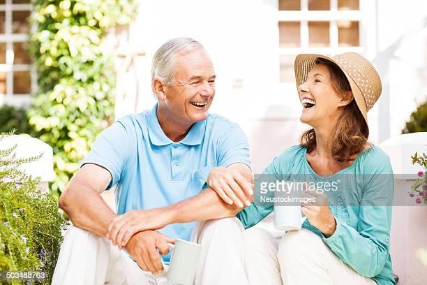 Senior Couple Taking Coffee Break While Gardening In Garden