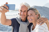 Happy romantic couple embracing on the beach and taking a photo with smart phone. Portrait of senior smiling couple taking a selfie in a summer vacation at sea. Happy mature couple take a picture at s