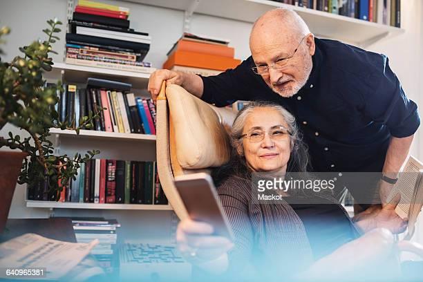 Senior couple taking selfie through mobile phone at home