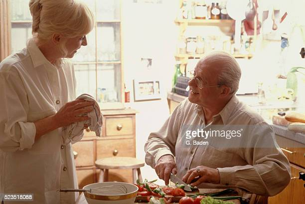 Senior couple talking and preparing food in kitchen