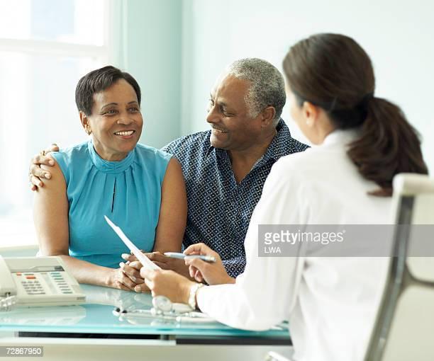 Senior couple talking to doctor, smiling