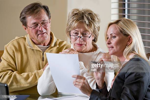 Senior couple talking with financial planner or consultant