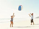 Senior couple throwing beach ball on beach