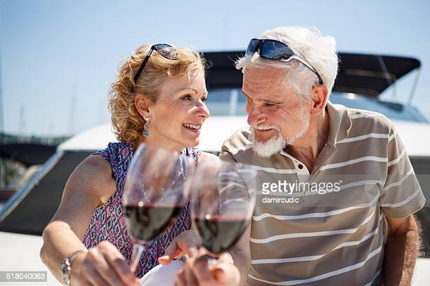 Senior couple toasting each other with wine on yacht