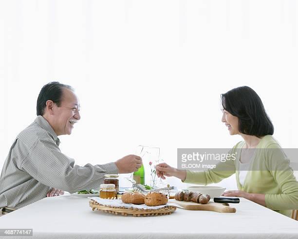 Senior Couple Toasting Glass Of Champagne