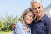 Portrait of senior couple embracing outside house. Smiling mature couple in garden embracing each other. Retired man with wife looking away.