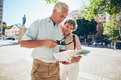 Mature couple standing outdoors in the city looking at a map. Senior man with his wife using city map for finding their location.