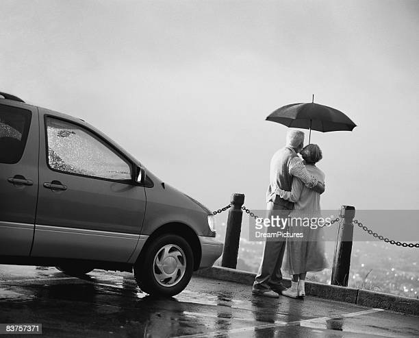 Senior couple under umbrella at scenic outlook