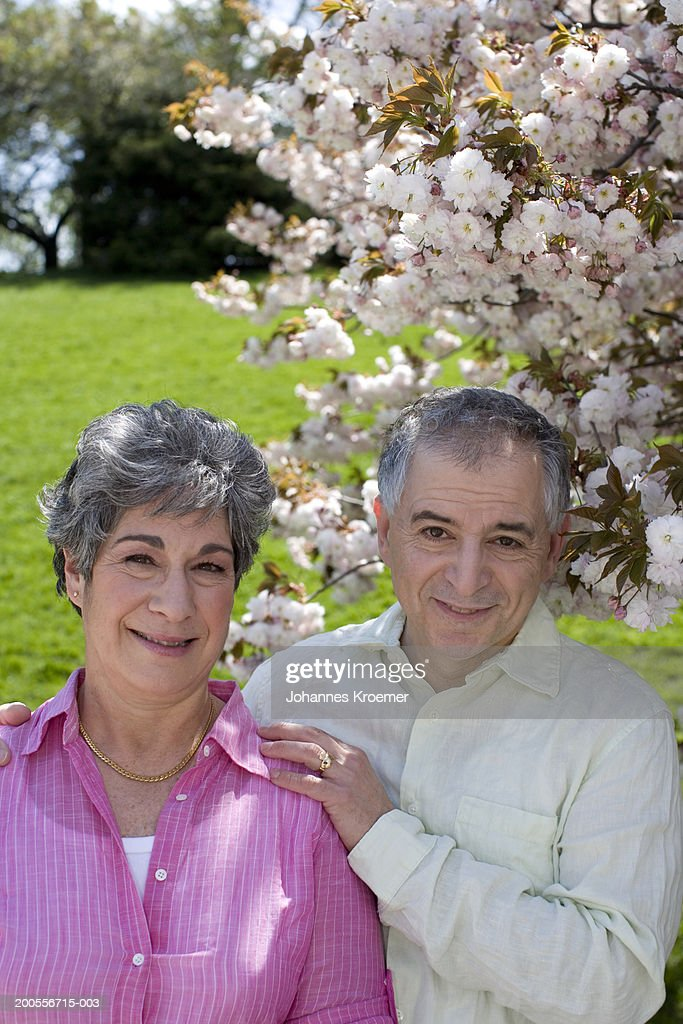 Senior couple underneath a cherry tree in bloom, portrait : Stock Photo
