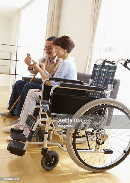 Senior couple using a smartphone on a sofa and a wheelchair