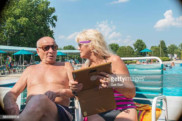Senior couple using digital tablet at outdoor swimming pool