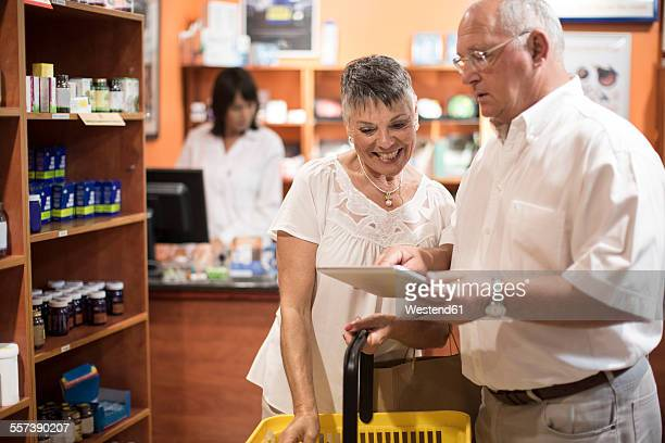 Senior couple using digital tablet in health shop