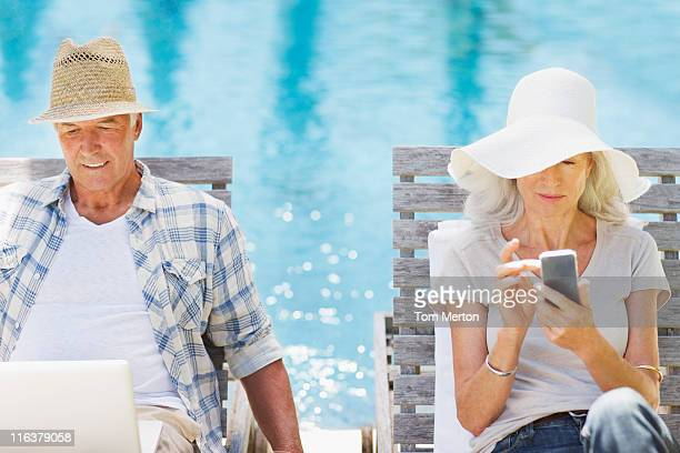 Senior couple using laptop and cell phone at poolside