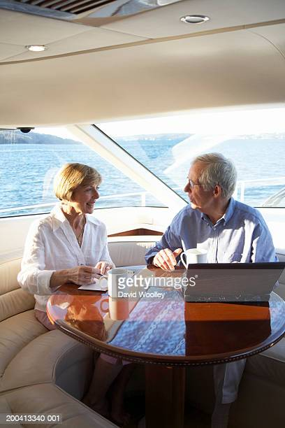 Senior couple using laptop and writing postcards on yacht, smiling