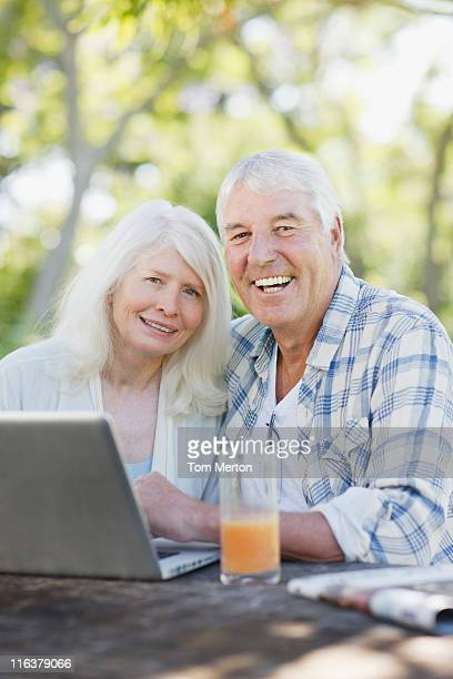 Senior couple using laptop at patio table