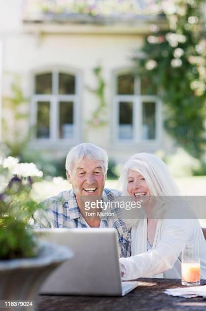 Senior couple using laptop at table in garden