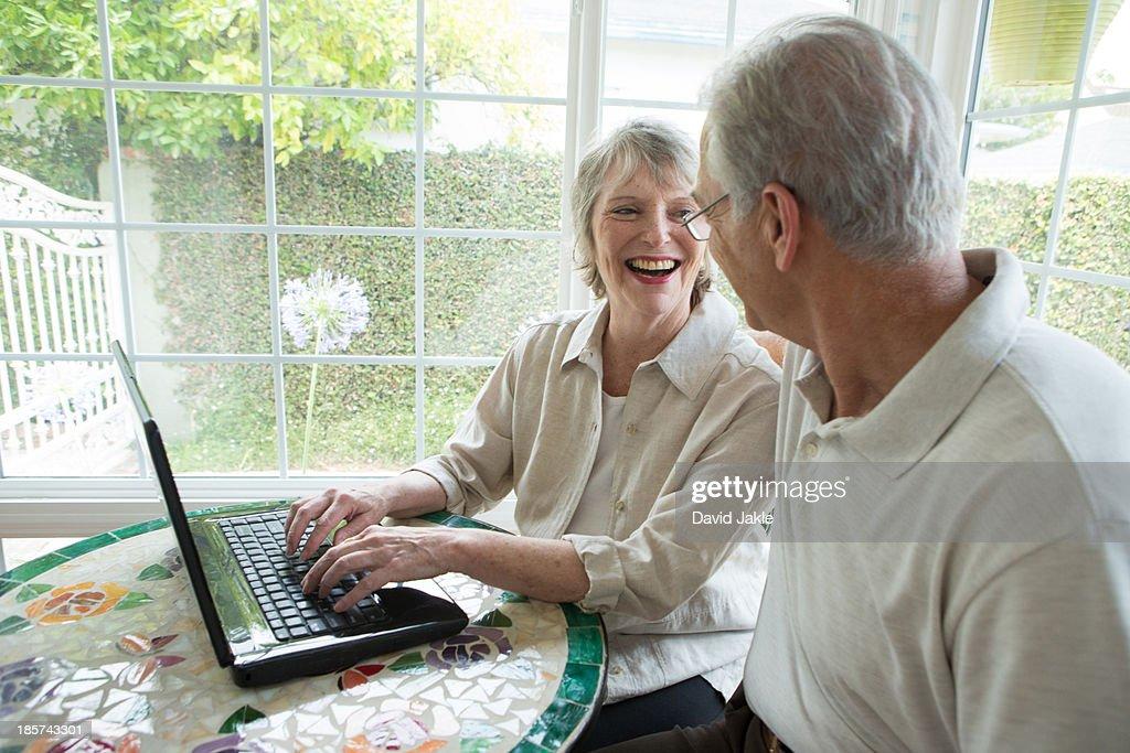 Senior couple using laptop in conservatory : Stock Photo