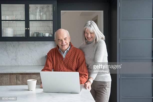 Senior couple using laptop in kitchen