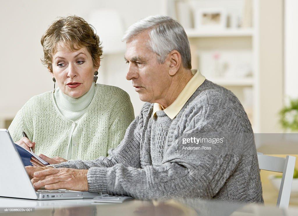 Senior couple using laptop in living room : Stock Photo