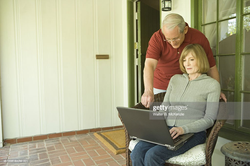 Senior couple using laptop on porch, man standing behind woman and pointing : Stock Photo