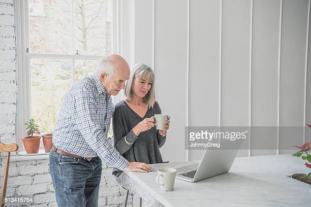 Senior couple using laptop, woman holding coffee